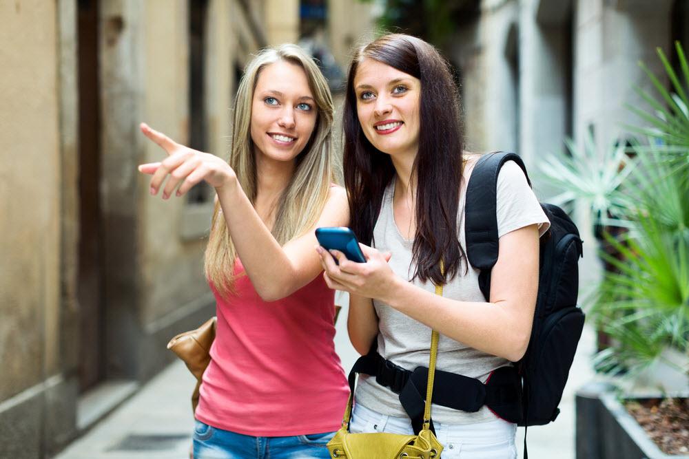 Frauen suchen nach Restaurant über Smartphone - finden passendes Restaurant über Facebook Werbung, die vom Restaurant geschaltet wird